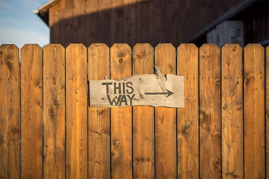 Valla de madera donde aparece un cartel que pone 'This way'