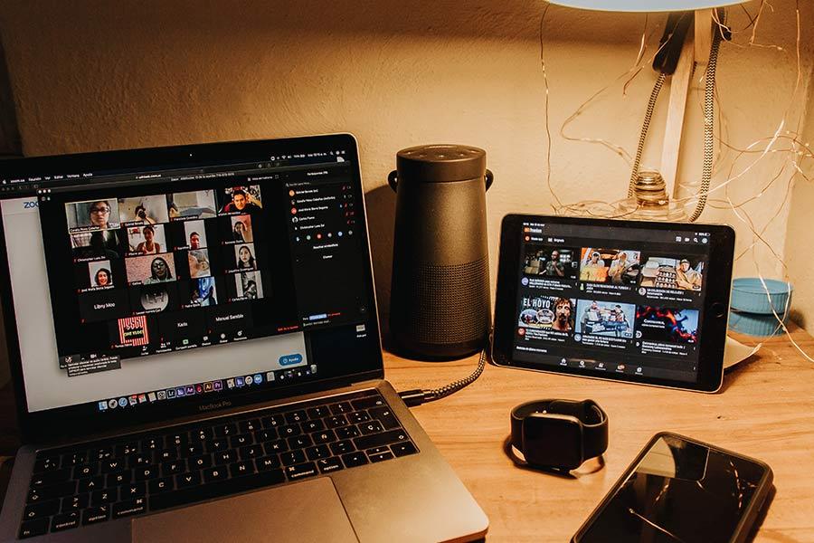 Mesa de escritorio con ordenador con videollamada de fondo y tablet con series