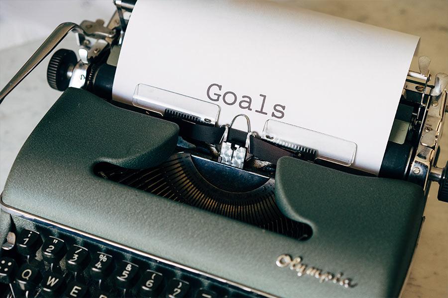 """Máquina de escribir con papel en el que pone """"Goals"""" para hablar de Objetivos Sistémicos Medibles"""