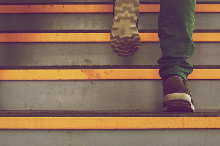 Persona subiendo escaleras como metáfora de liderazgo creciente